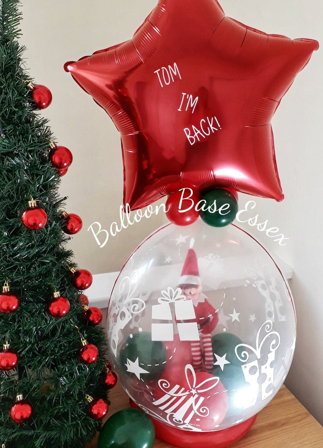 Elf inside a balloon with red star balloon on top